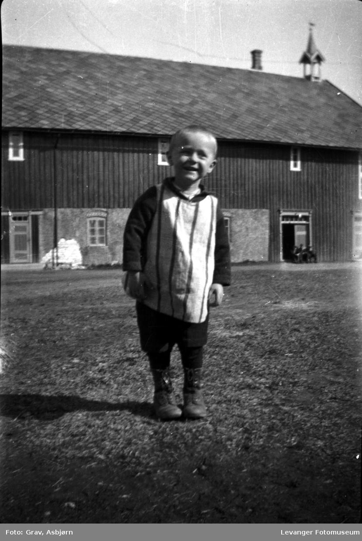 Portrett. av gutt på gårdsplass.