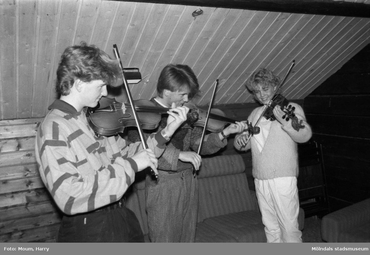 """Ungdomar spelar violin i ABF-stugan i Lindome, år 1985. """"Ungdomarna Peter Sandin, Jonas Persson och Sofia Johansson tycker det är kul i ABF-stugan under måndagskvällarna.""""  För mer information om bilden se under tilläggsinformation."""