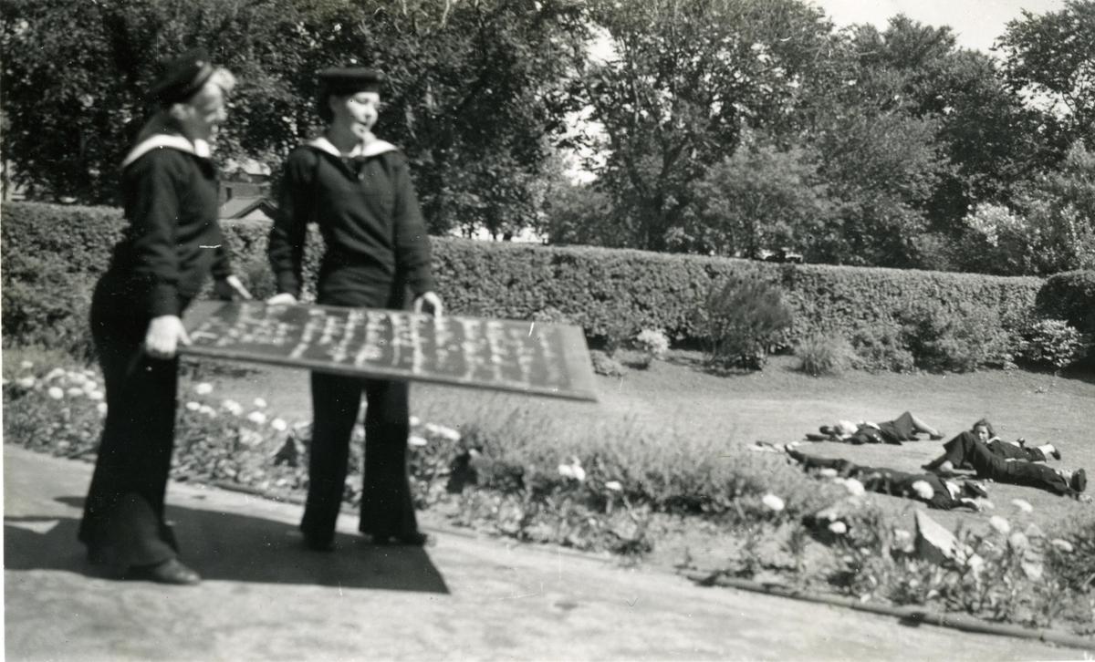 Motiv: Marinens Kvinnekorps 1942-1945. Knutetavle og jenter på plenen