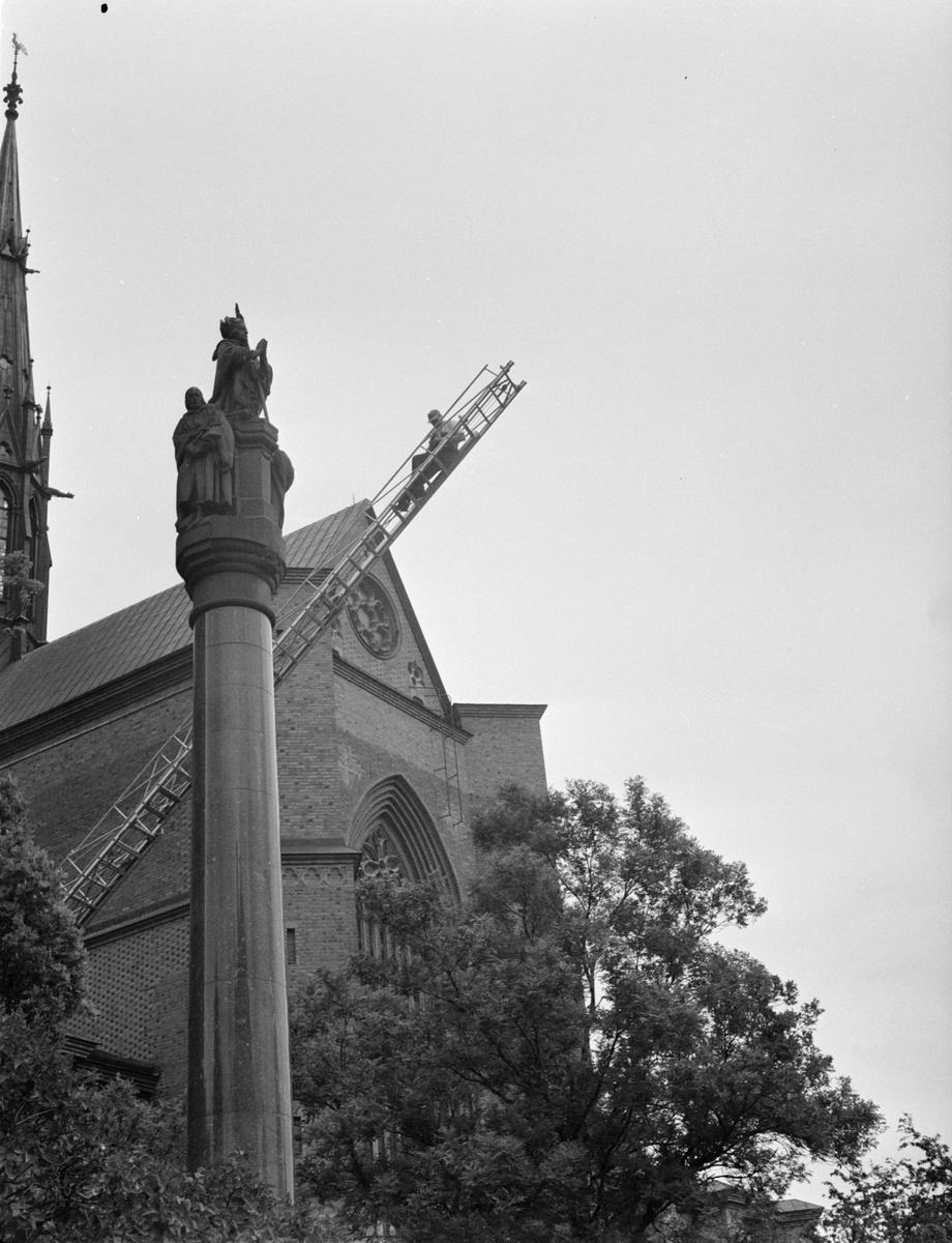 Man på hög stege framför Uppsala domkyrka och statyn av ärkebiskop Jakob Ulvsson, Uppsala