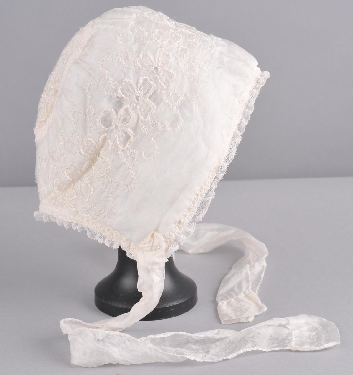 Kvit luve av silke med maskinbroderi. Luva er eit rektangulært stykke stoff som har saum midt bak og rynker mot ein sirkel med diam. på 9cm. Saumen er skjult av ei kvit kroklisse i silke. Blondedekor langs ytterkant  framme og i nakken på luva, med kroklisse av silke over. Foret på luva har same snitt som ytterluva, er av bomullslerret og vattera. Knytebanda er  av kvit silke.