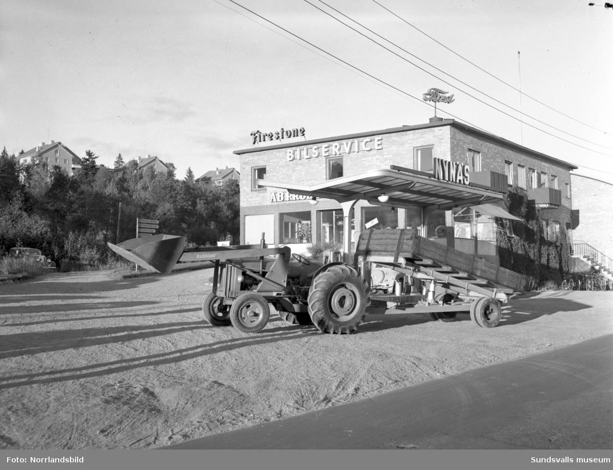 """En jordbrukstraktor med skopa (""""Hudiklast"""") och släpvagn med tipp står utanför Fröberg & Sjöbergs Bilservice vid Norra kajen, Tivoli."""