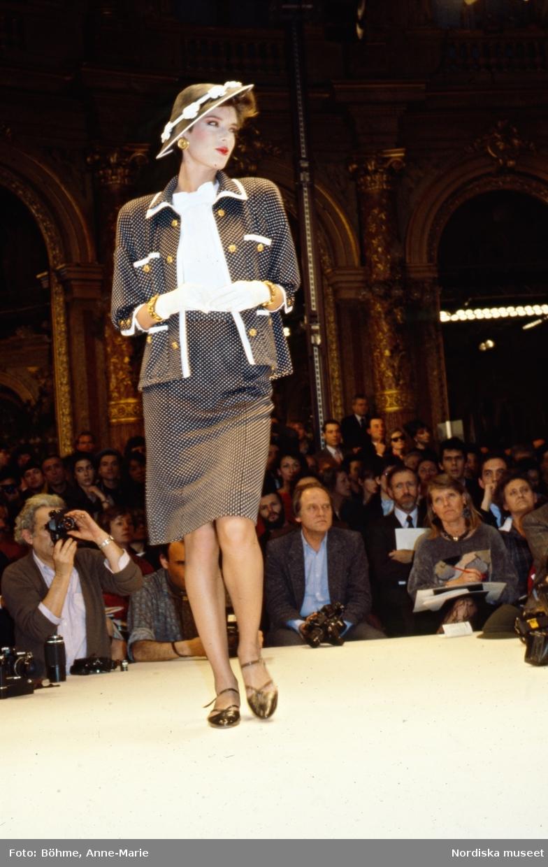 Modevisning. Modell i dräkt, vita handskar och hatt. Från Chanel.