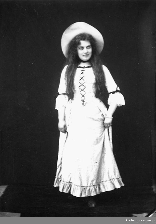 Tonårsflicka kostymerad  i vit klänning med snörliv och bredbrättad hatt.
