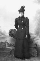 Kvinna i svart dräkt med pälskrage och hatt. e53cc0e5ca4ef