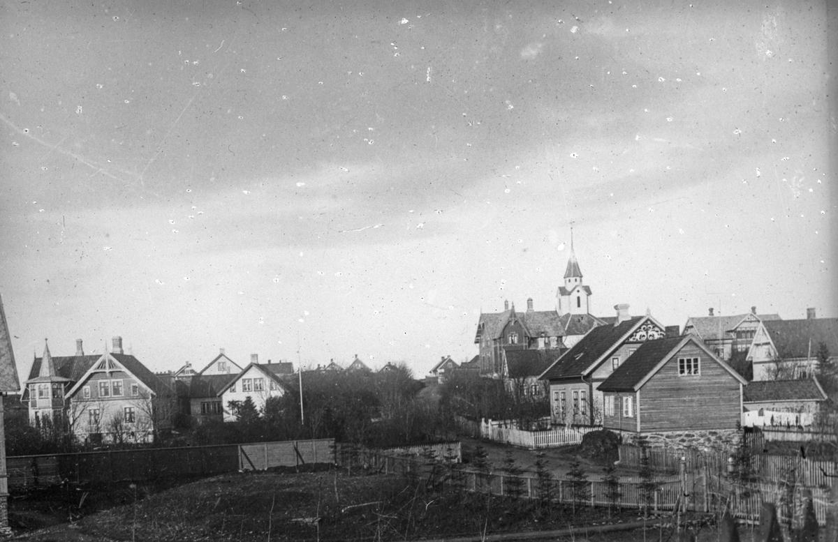 Lothemarken. Skåre kirke i bakrunnen. Trehus til venstre i bakgrunnen. I forgrunnen noen trær og to gjerder.