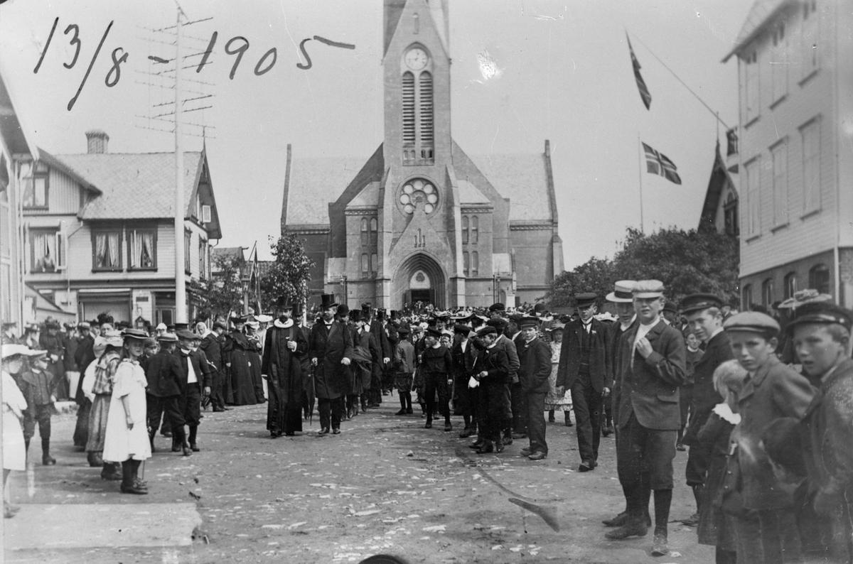 Torvet, utenfor Vår Frelsers kirke 13. august 1905, dagen for folkeavstevningen om unionen med Sverige.  Flere personer. Barn i fogrunnen til høyre.  Kirken i bakgrunnen. Trehus til venstre og høyre. Norsk flagg i bakgrunnen til høyre.