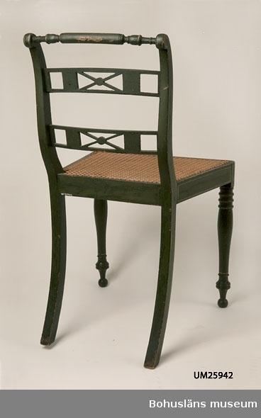 Senempirestol. Grön med vita kantlinjer. Svarvade framben. Bakåtsvängda, fyrsidiga bakben. Svängda ryggståndare. Rygg med tre horisontala spjälor. Den översta är svarvad. De två nedre är rektangulära och genombrutna. Sits av flätad rotting. Sitsen och färgen är sekundär (från 1800-talets slut). Stolarna har tillhört en uppsättning om tolv stolar som stod i direktionsrummet på Kampenhofs bomullsväveri och spinneri, Uddevalla.  Nordverk AB, Uddevalla förvärvade 1954 Kampenhof genom sin chef Lennart Ullberg. I lokalerna vid Västerlånggatan, Uddevalla, drevs verksamhet innan de byggde nytt på Kuröds industriområde, Uddevalla. Givaren erhöll UM025941 och UM025942 inklusive ytterligare elva stolar från direktionsrummet på Kampenhof som gåva av Lennart Ullberg.  Stolarna har därefter delats upp i grupper om fyra och fyra och spritts till givarens bekanta. Något bord som ingått i möblemanget har aldrig familjen sett eller hört talas om  (uppgift den 4 september 2008 från givarens dotter).  September 2008: Enligt antikvarie Birgitta Martinius, Mölndals museum, som undersökte vad som finns i museets samlingar av Lindometillverkade möbler, så är detta inte en stol som kan hänföras till detta område eller någon annan svensk tillverkare. Flera detaljer var okända för henne exempelvis de rektangulära formerna i ryggtavlan samt avslutningarna nertill på frambenen. Eventuellt engelsk tillverkning.