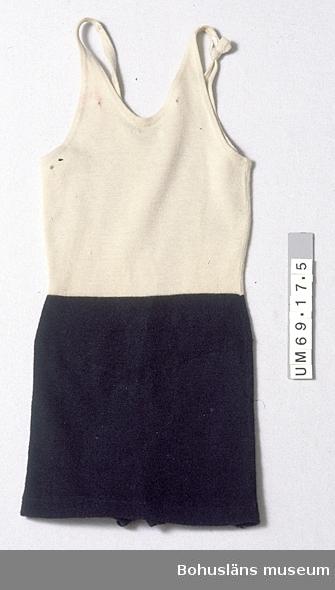 Föremålet visas i basutställningen Kustland,  Bohusläns museum, Uddevalla. 594 Landskap BOHUSLÄN 503 Kön KVINNA 433 Teknik MASKINTILLVERKAT, STICKAT; MASKINSYTT  Ovanför midjan av vit (gulnad) och nedanför av svart ylletrikå. Har kjol utanpå en byxdel (eg utformad som en kort klänning med isydd invändig byxdel). Med smala axelband, det ena fast, det andra delat; nu är bakre delen knuten i knapphålet på främre delen. Knapp saknas. Djupare ringad i ryggen än framtill. Upptill bak finns fastsydd tygetikett med två damer i baddräkt och badmössor samt texten: AJCO. Etikettens färger: vit bakgrund, grön text, rödgult, rödtonat beige och grönt i bilden. Några hål och tre lagningar (stoppningar) i vita delen. Bruna fläckar vid midjan bak, ljust röd missfärgning vid vänster axelband på framsidan.  Litt.: Costantino, Maria, 30-talets mode, Bokfabriken fakta Malmö 1993, s. 42 och 54.  Larsson, Marianne: Från badkostym till bikini ur Fataburen 1998, s. 136-160.  Rowland-Warne, L, Fakta i närbild Kläder, Bonniers Juniorförlag AB Stockholm 1993, s. 34-35. 990 Katalogiserat 1997-09-18 VBT