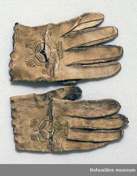 """Användningstid och tillverkningstid uppskattade. Handgjorda handskar av vitt skinn (gulnat, mörknat) med ett stiliserat blommönster med runda mönsterformer broderat i plattsöm, bred stjälksöm och langett. Sömmen runt tummen är markerad med en flätsöm. Färgerna i broderiet är beige, ljust gulgrönt, blått och ljusgult. Vantarna är märkta UM 6:B och UM 6:C. Den blivande bruden fick s k brudhandskar som gåva av fästmannen. Hon skulle bära dem på bröllopet, men de användes även senare till högtid. Slitna. Hål eller lagningar på flera fingertoppar. (Spik?)hål genom pekfingrarna. Sprickor i skinnets ytlager. Delar av broderiets tråd bortsliten. Mycket smutsiga. Insidan nedsmutsad till mörkbrun färg.  Litteratur: Nylén, Anna-Maja, Folkdräkter ur Nordiska  museets samlingar, Nordiska museets handlingar 77, Lund 1971, sid. 67-70. Widhja, Inger, Takhimlar och brudhandskar Folklig textiltradition i Västergötland, Skrifter från Skaraborgs länsmuseum nr 12, Skara 1990, sid. 132-133.  Ur handskrivna katalogen 1957-1958: Sidenmössa o.brudhandskar a) Mössan, av blått siden på styv stomme, broderad. luggsliten, mkt blekt. b)-c) Handskar, ett par, av skinn m. broderier, ngt sönder.  Lappkatalog: 77  Se UM2048A-C under  Enligt uppgifter på diarienummer 184/69 KVINNLIGA DRÄKTPLAGG FRÅN BOHUSLÄN TILL UDDEVALLA MUSEUM: 6 b Ör-ringar 3 st. av silver. 1 par 2 cm. i diam., den tredje 1,7 x 1,6 cm i diam. """"De höra till en kvinnodräkt från Bohuslän"""". [Troligvis rör beskrivningen på UM002048 Öronringar som kom in samtidigt med mössa och handskar katalogiserade under UM6; kanske de sedan hamnat vid sidan om och därför senare getts ett annat UM-nummer.]"""