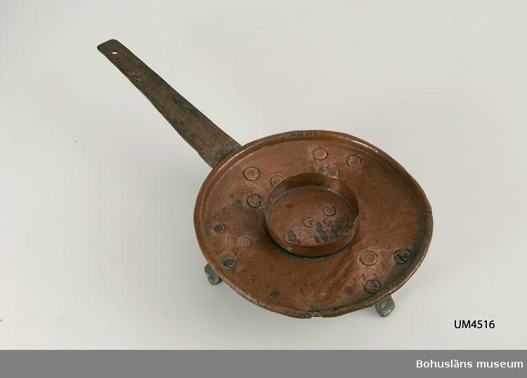 Ur handskrivna katalogen 1957-1958: Brasbricka L. m. handt. 37; D. c:a 19; H. 6-7 cm; av koppar; 3 fötter av koppar, handtag av järn. Hel.  Lappkatalog: 90