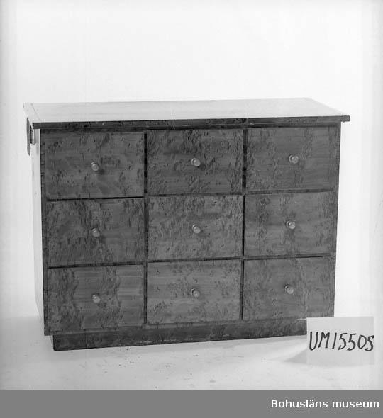 """Byrå med nio lådor i tre etage. Lådorna är tillverkade av margarinlådor från """"VICTORIA NORMA MARGARIN"""" Målad med gulgrön ådringsmålning. Runda knoppar av metall. Den tillverkades av Verner Olsson på 1930-talet för att ingå i köksutrustningen i familjens hus på Edingsvägen 31."""