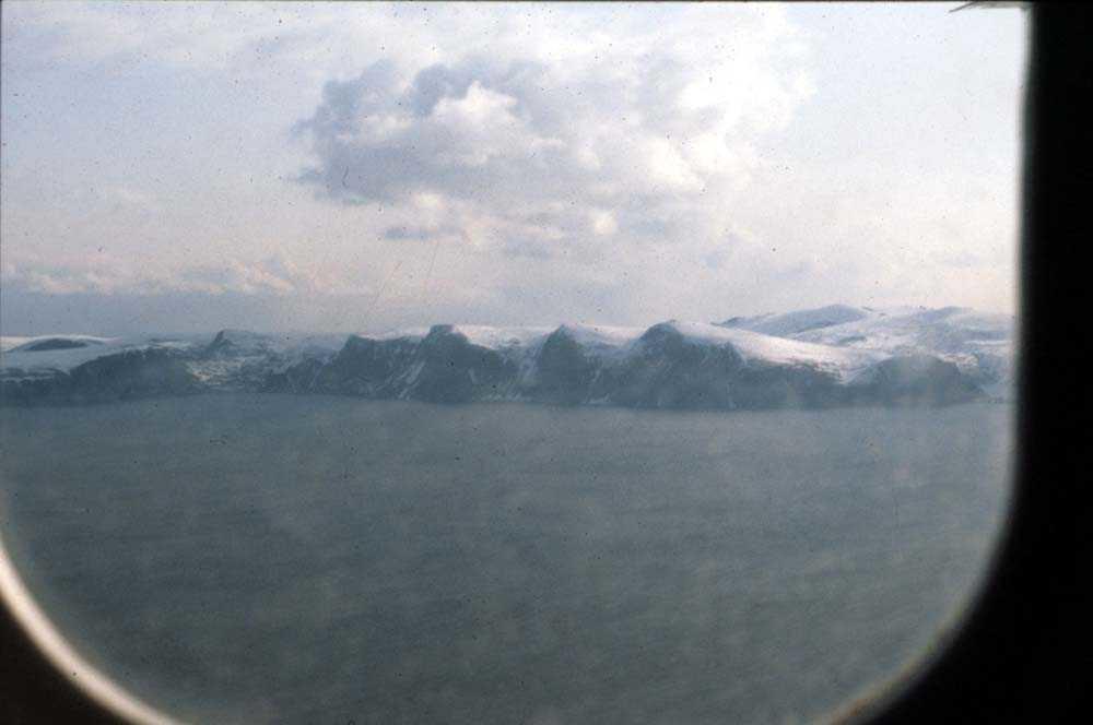 Luftfoto. Fjellrekke langs fjorden dekket av sne. Ett sted i nord. Foto tatt fra DHC-6-300 Twin Otter fra Widerøe.