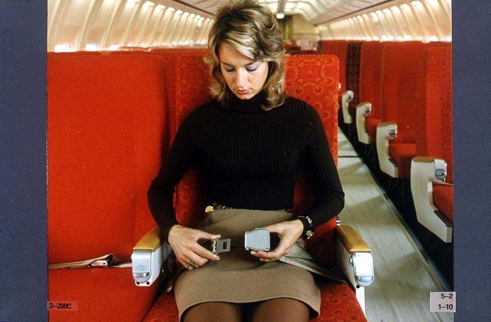 En person som sitter i en stol i kabinen på ett fly, Boeing 737-200, og tar på seg et sikkerhetsbelte.
