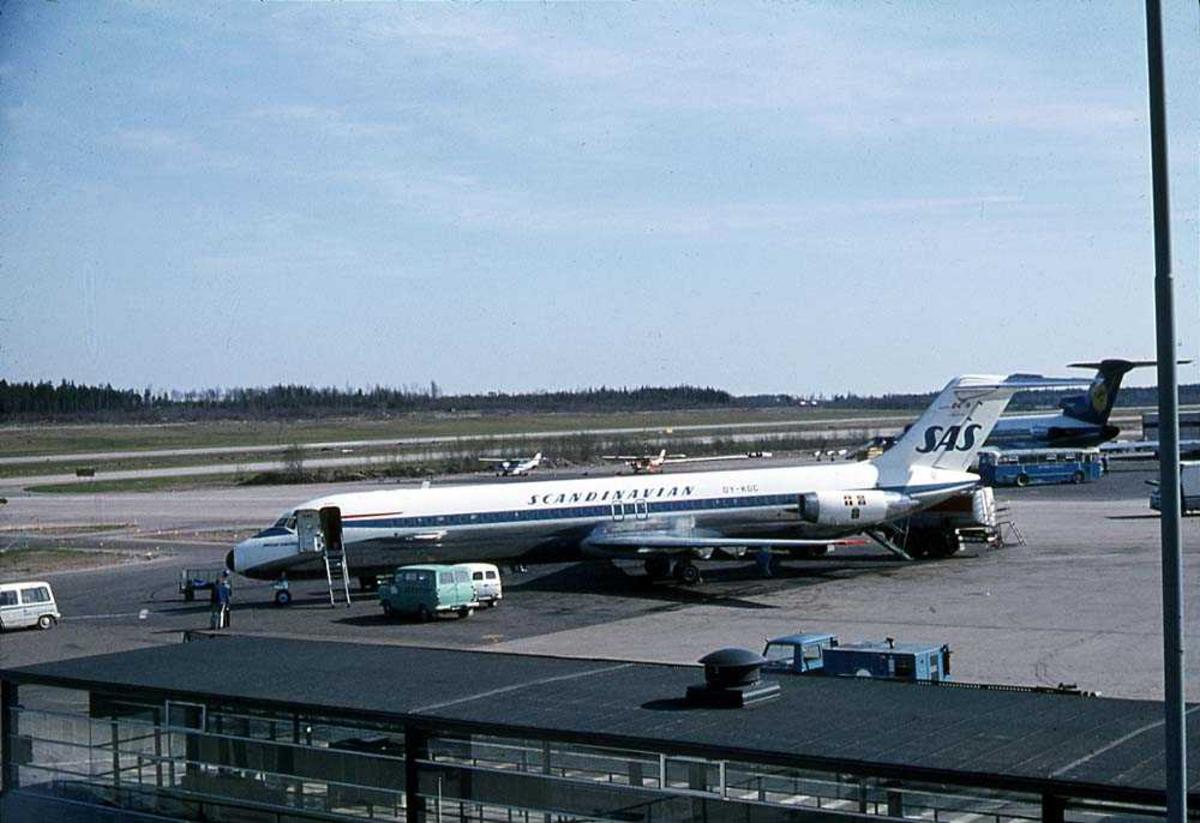 """Lufthavn. Ett fly på bakken, McDonnell Douglas DC-9-41 OY-KGC """"Helge Viking"""" fra SAS. Flere andre fly i bakgrunnen."""