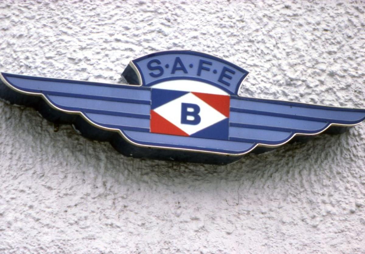 Landskap. Braathens SAFE's logo på en murvegg.