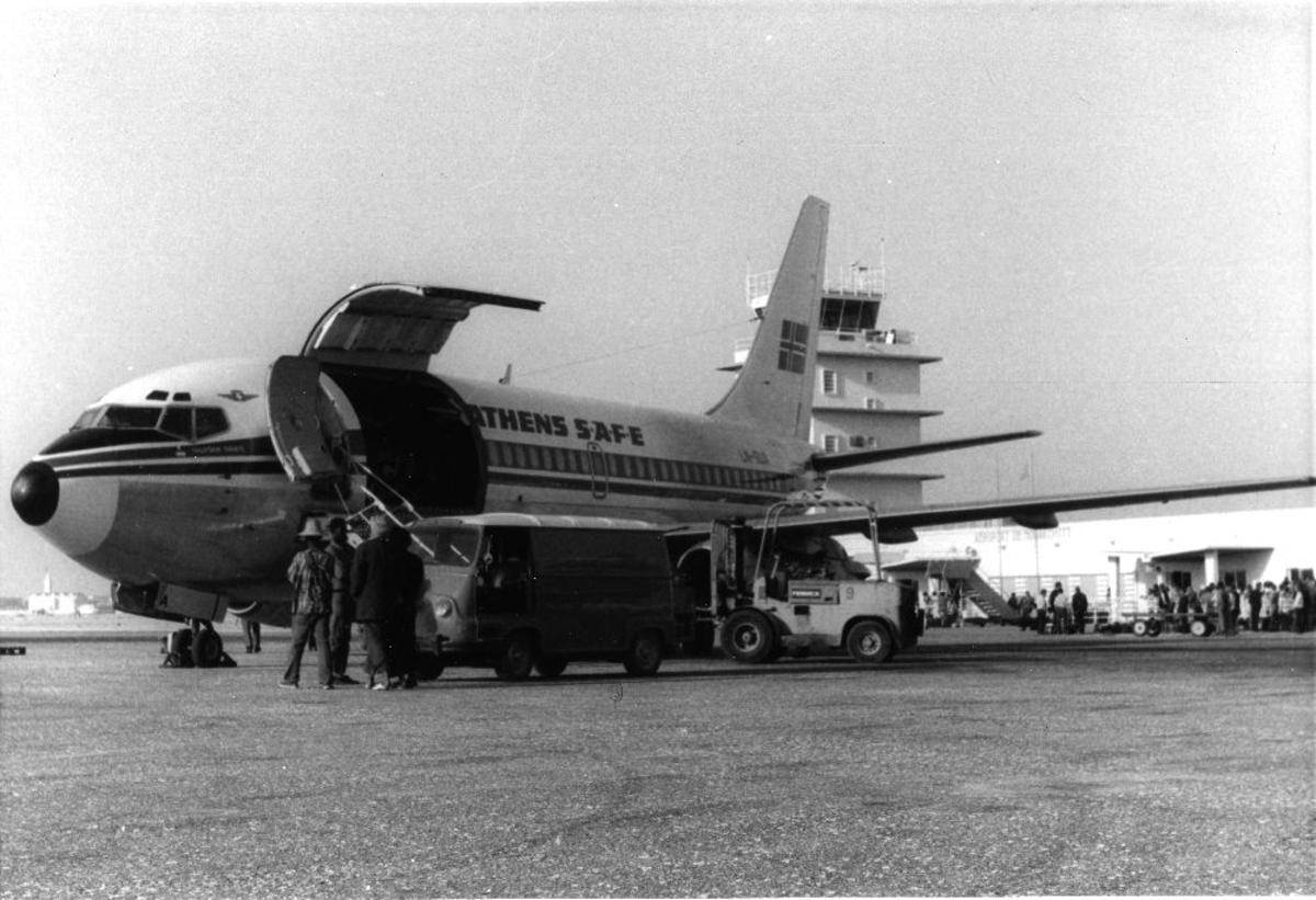 Lufthavn/Flyplass. Ett charterfly fra Braathens SAFE parkert. Biler og personer utenfor. Flytårn i bakgrunnen.
