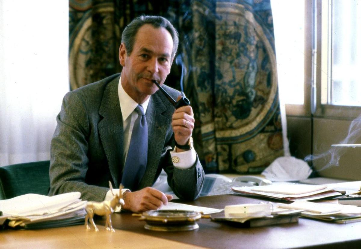 Portrett. En person ved sitt skrivebord holder en pipe i hånden.