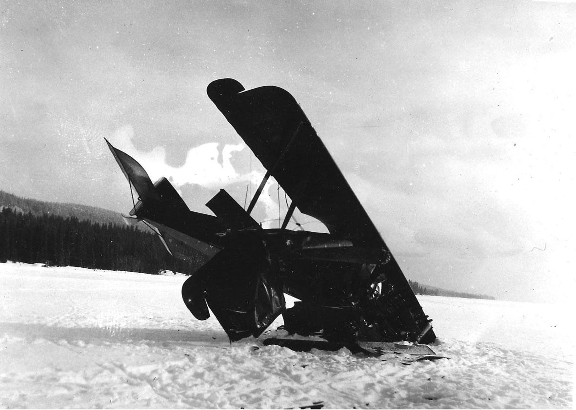 Åpen plass, lufthavn? ett fly, havarert Kaje, med framenden og spissen på ene vingen ned i bakken. Snø.