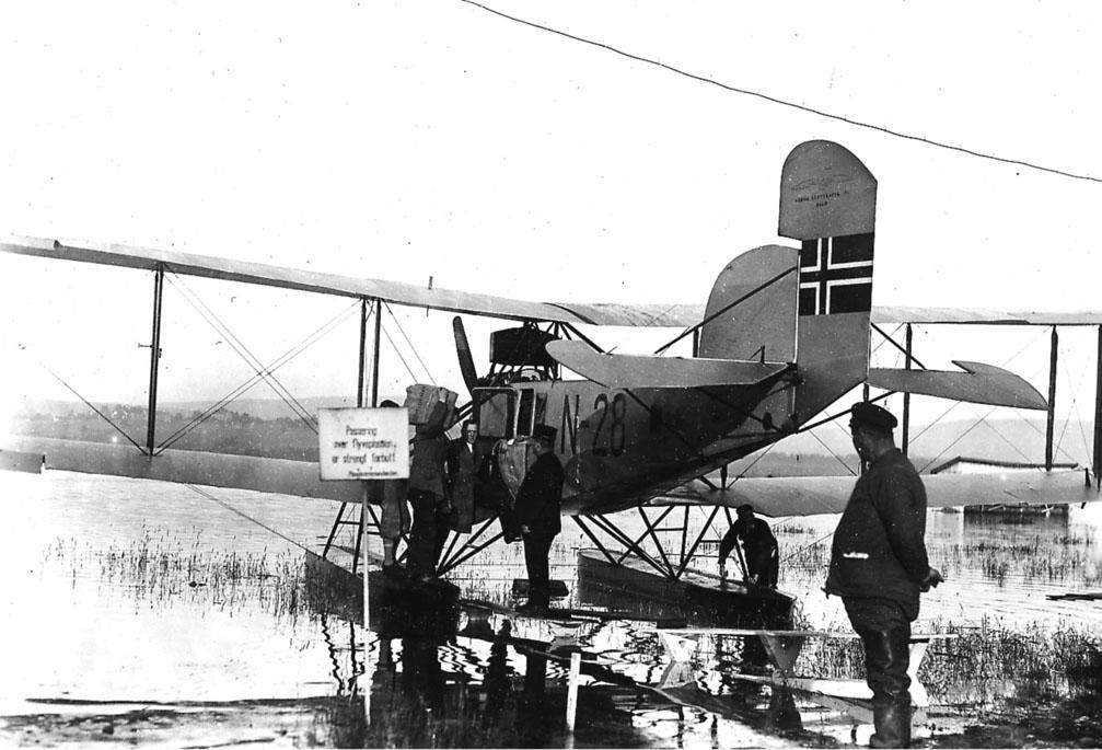 Sjøflyhavn, ett fly på vannet, LFG V.13 Strehla, N-28. Flere personer ved flyet, Aftenposten lastes ombord.