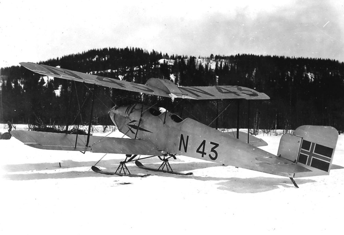 Åpen plass, ett fly på bakken, Simmonds Spartan I, reg no  N 43, med skiunderstell. Snø på bakken.