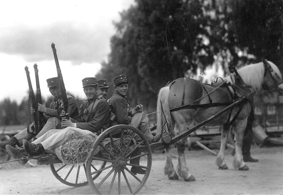 Hest og kjerre, fire personer, soldater med geværer  sitter på hestevogna.