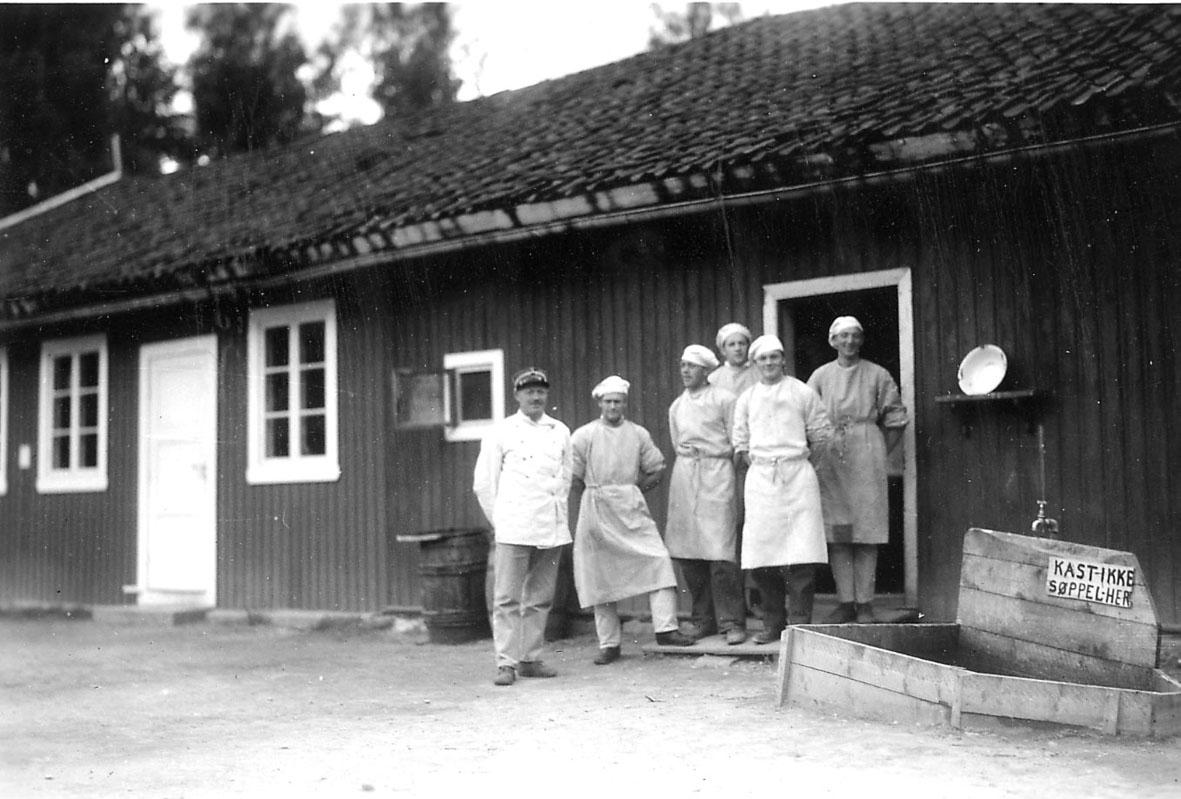 Bygning/messe  Flere personer ved en av inngangsdørene. Kjøkkenpersonale, en med militærlue. Ant. fra en miliitærleir.