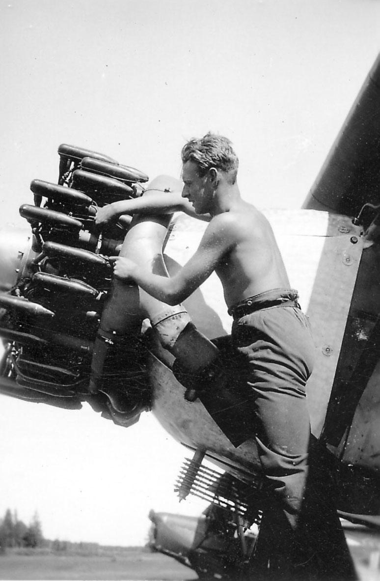 Detalj av flymotor 11, en person arbeider med motoren til ett fly, Fokker CVD.