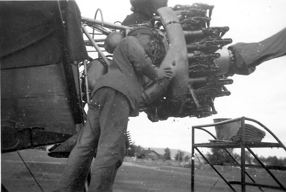 Åpen plass, ant. lufthavn. Detalj av flymotor,  en person arbeider med motoren på ett fly, Fokker CVD.