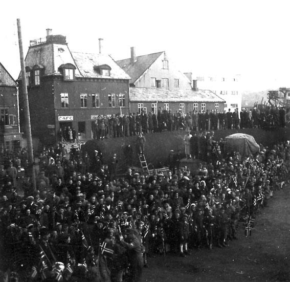 """Frigjøringsdagene i Bodø etter krigen 1940 - 1945. Mange personer samlet nede på kaiområdet. Bygning bak med påskrift """"CAFE"""". Kullkranen til Jakhelln t.h."""