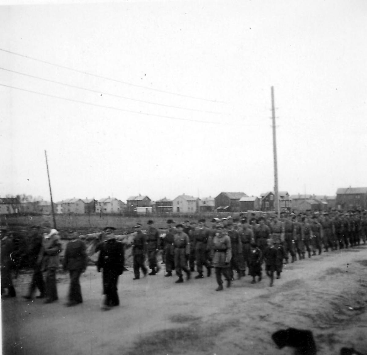 Frigjøringsdagene i Bodø etter krigen 1940 - 1945. Mange personer går i tog, de fleste er soldater. Fra Svenskbyen.