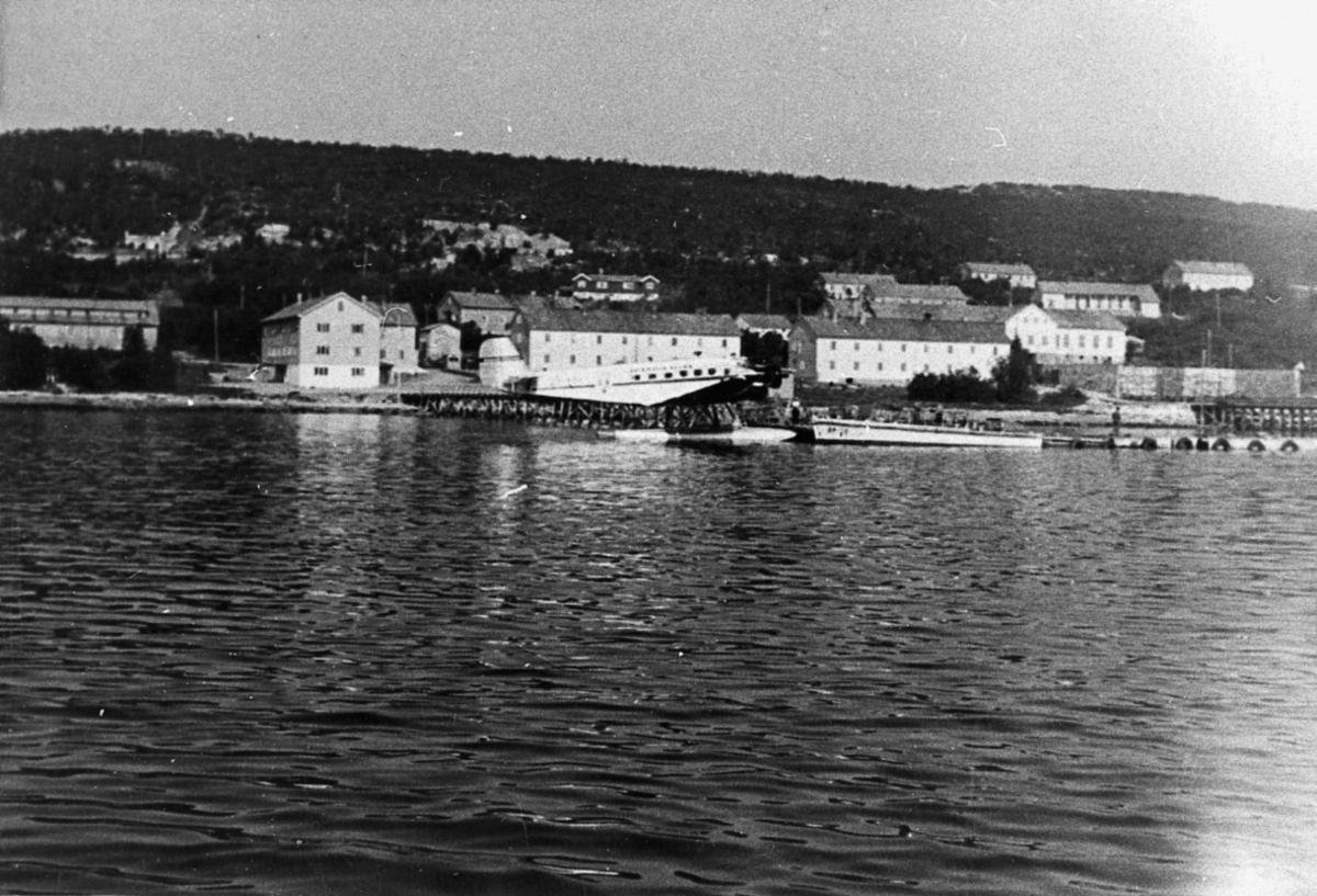 Sjøflyhavn, Ett fly i vannkanten, Junkers, fra SAS, ved kai. En båt til høyre. Flere bygninger inne på land. Hav i forgrunnen.