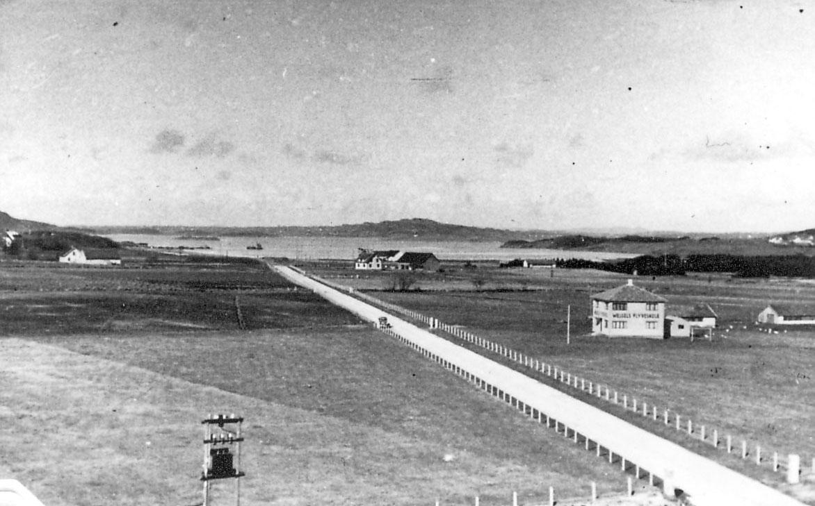 """Dyrka mark, en vei, noen bygninger. Havet bak. Bygning t.h. med påskrift """"Wessels Flyvesskole"""" e.l."""
