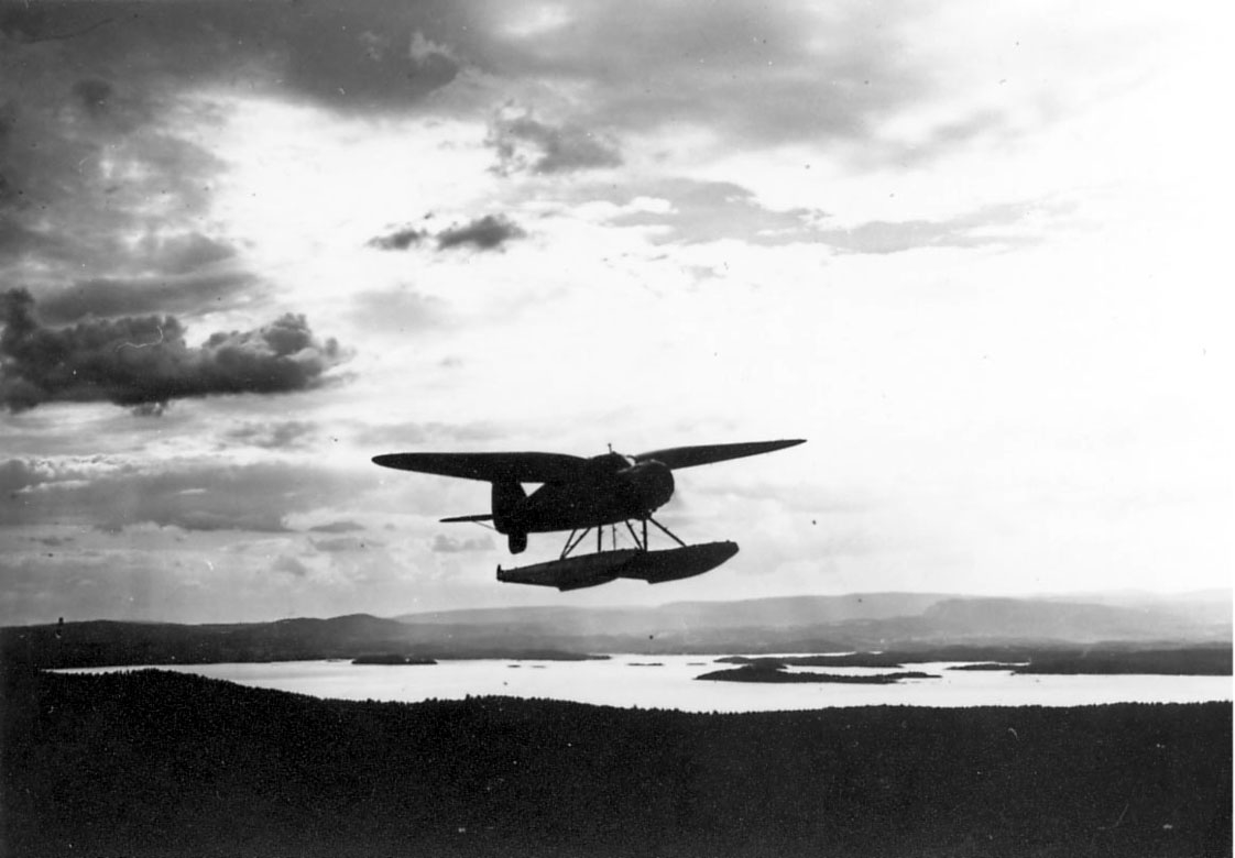 Luftfoto, ett fly i luften, landskapet sees nedenfor. Stinson SR.8EM fra Widerøe.