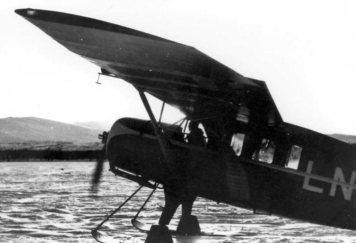 Ett fly på bakken, med skiunderstell, på åpen plass. en person, flyger, sees gjennom vinduet i cockpit. Bellanca 31-55 Senior Pacemaker, LN-ABO. Fra Widerøe.