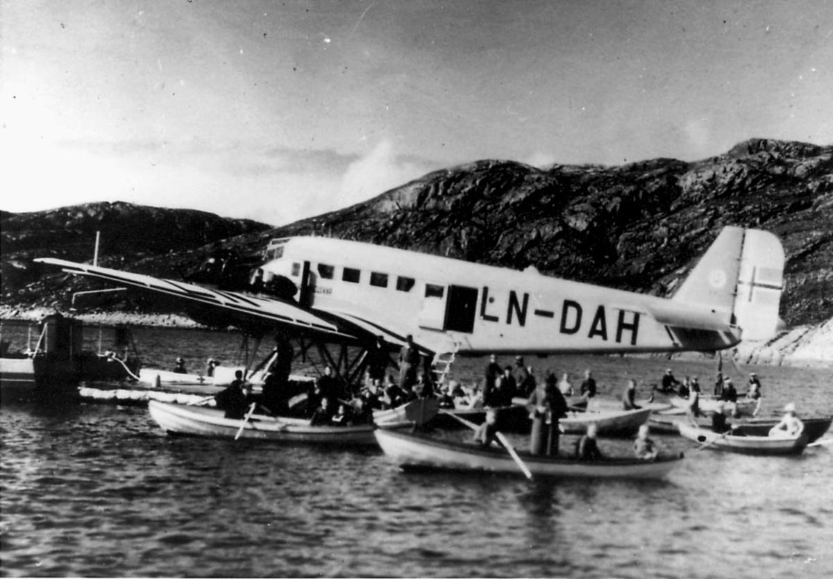 Ett fly ligger i vannkanten, Junkers Ju52/3mg2e, LN-DAH. Flere robåter med flere personer ombord, ved flyet. (Passasjerer?)