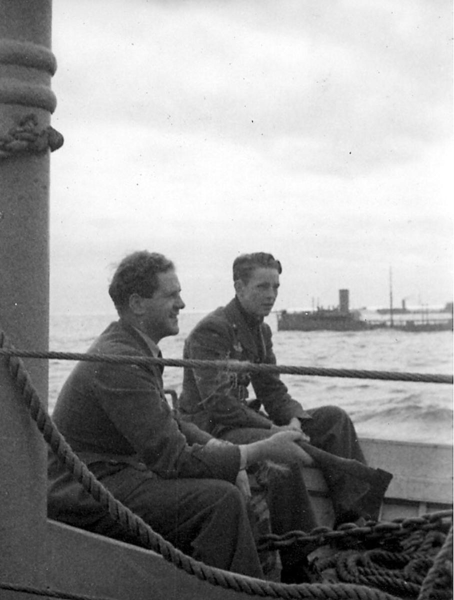 Portrett, to personer, militære, i militæruniform ombord i fartøy. to andre fartøy bak. Åpent hav. Ant. fra konvoy.