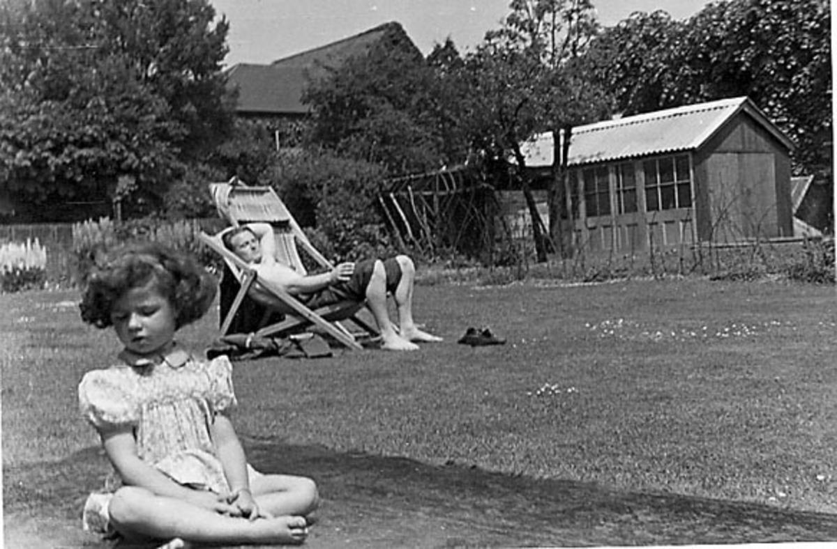 Portrett, en person sitter i en campingstol. Foran sitter et barn. Tatt utendørs.