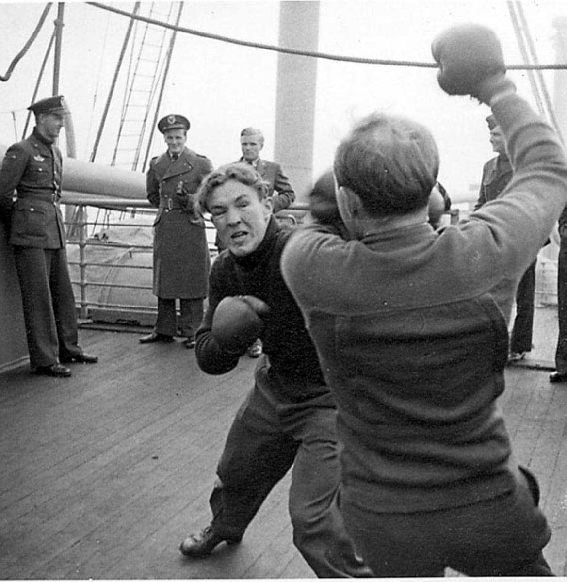 """Portrett, 2 personer, militære, i forgrunnen, i """"boksekamp"""" ombord i et fartøy. Andre personer står og ser på"""