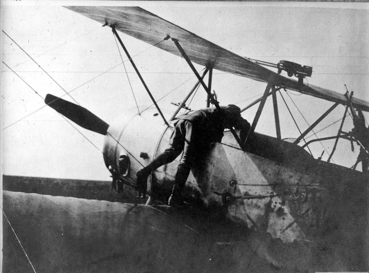 Fly, Sopwith 1 1/2 Strutter. Skrått bakfra, forparten. Står på bakken. 1 person i arbeid med flyet.