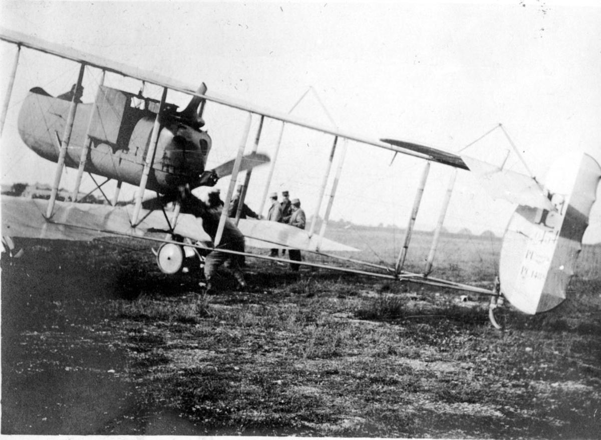 Fly, Maurice Farman. Sett fra siden. Står på bakken. Noen personer ved flyet.