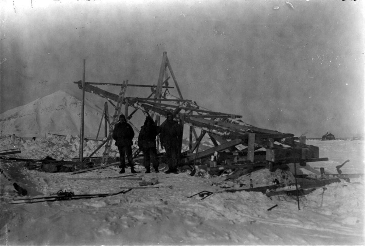 Mast, tårn, ligger på bakken. 3 personer står foran. Snø på bakken. Fjell bak.