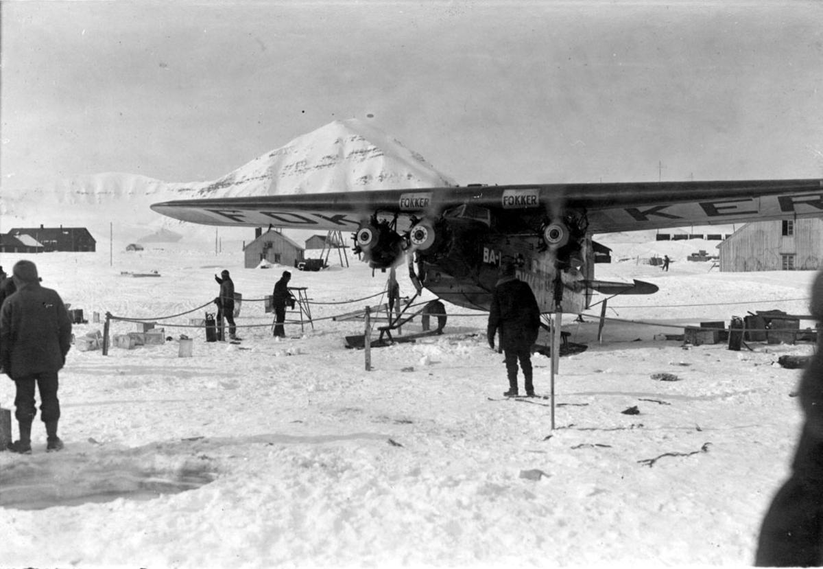 """Fly, propellfly, på bakken, Fokker FVII """"Josephine Ford"""", med motorene i gang. Noen personer ved flyet, en del utstyr. Noen bygninger bak, fjelltopp."""