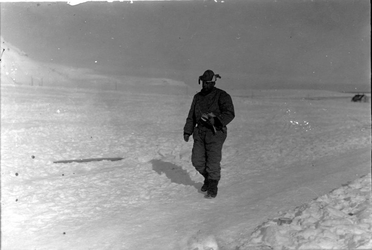"""Portrett, 1 person i flygerdrakt. På vei ombord i luftskipet """"Norge""""? Bygning  i bakgrunnen, snø på bakken."""