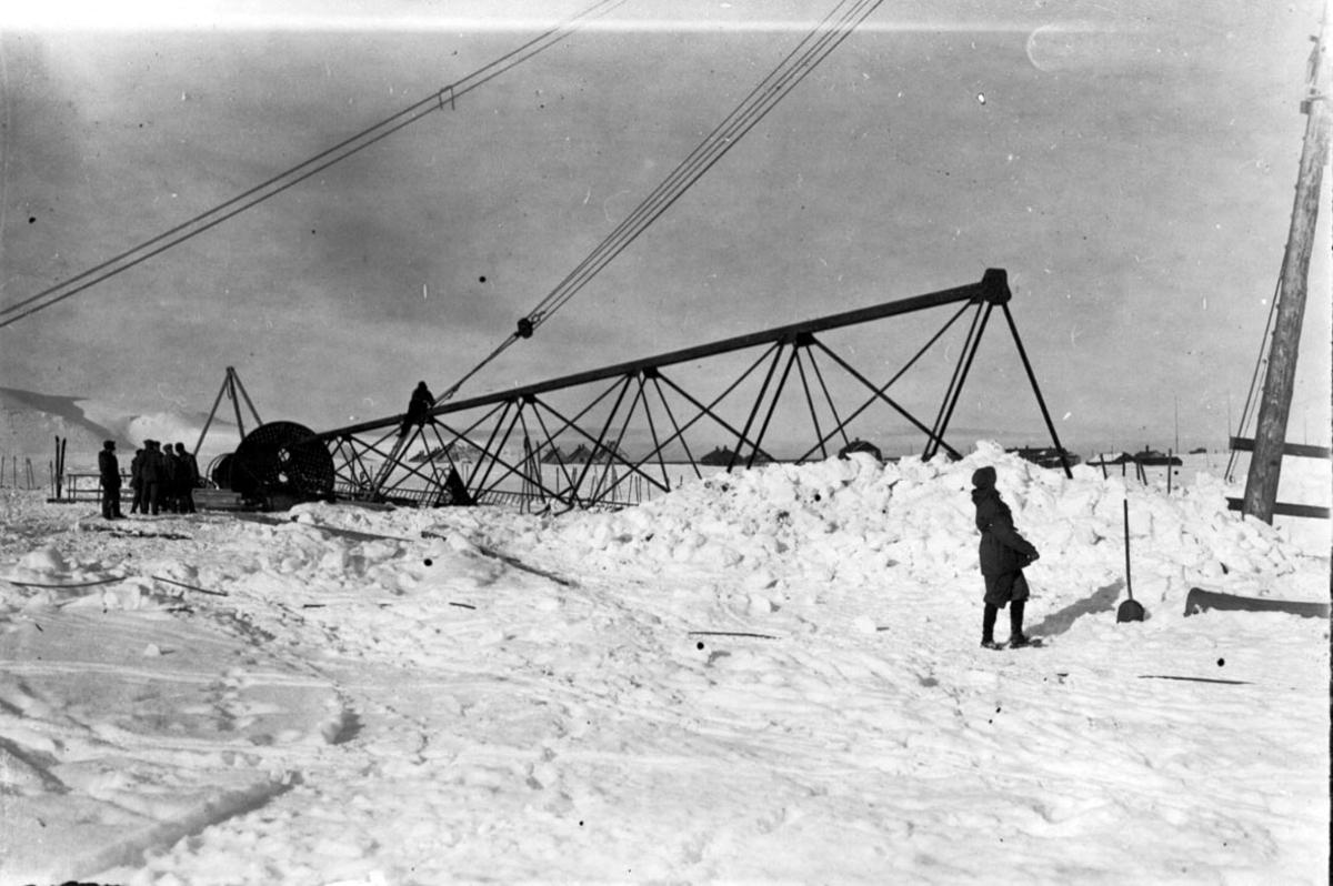 "Fortøyningsmasten til luftskipet ""Norge"" før den heises på plass. Flere personer i arbeid. Snø på bakken."