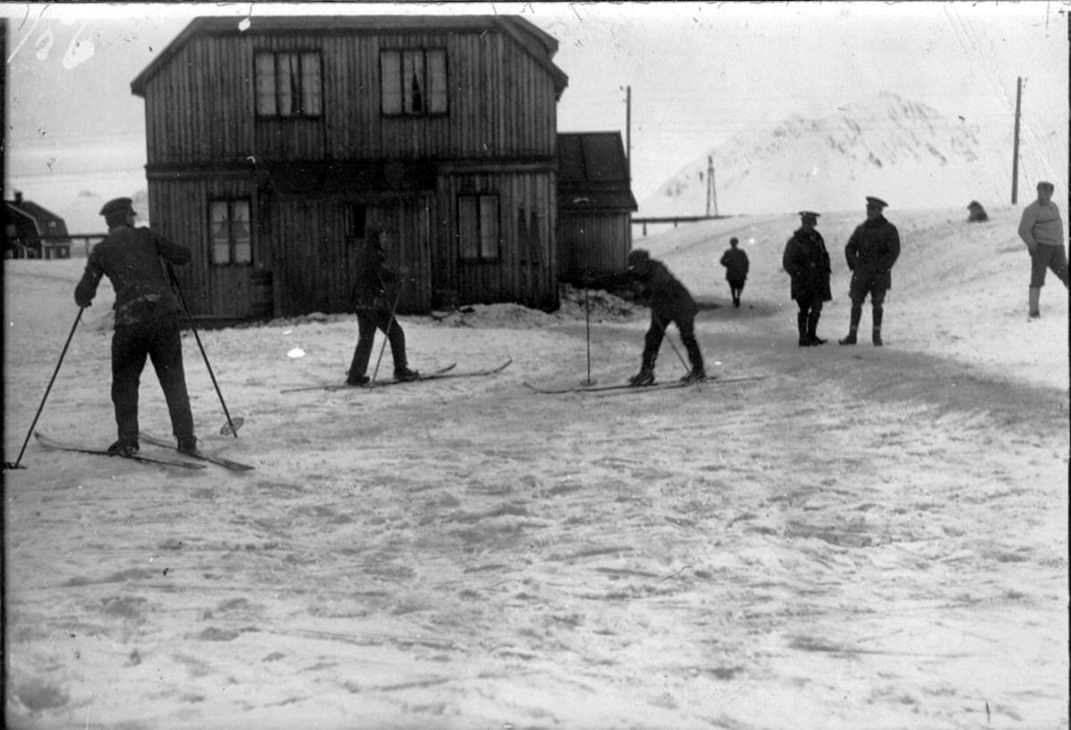 Flere personer, de fleste med ski, skitrening. 1 person instruerer. 2 bygninger, snø på bakken, fjell bak.