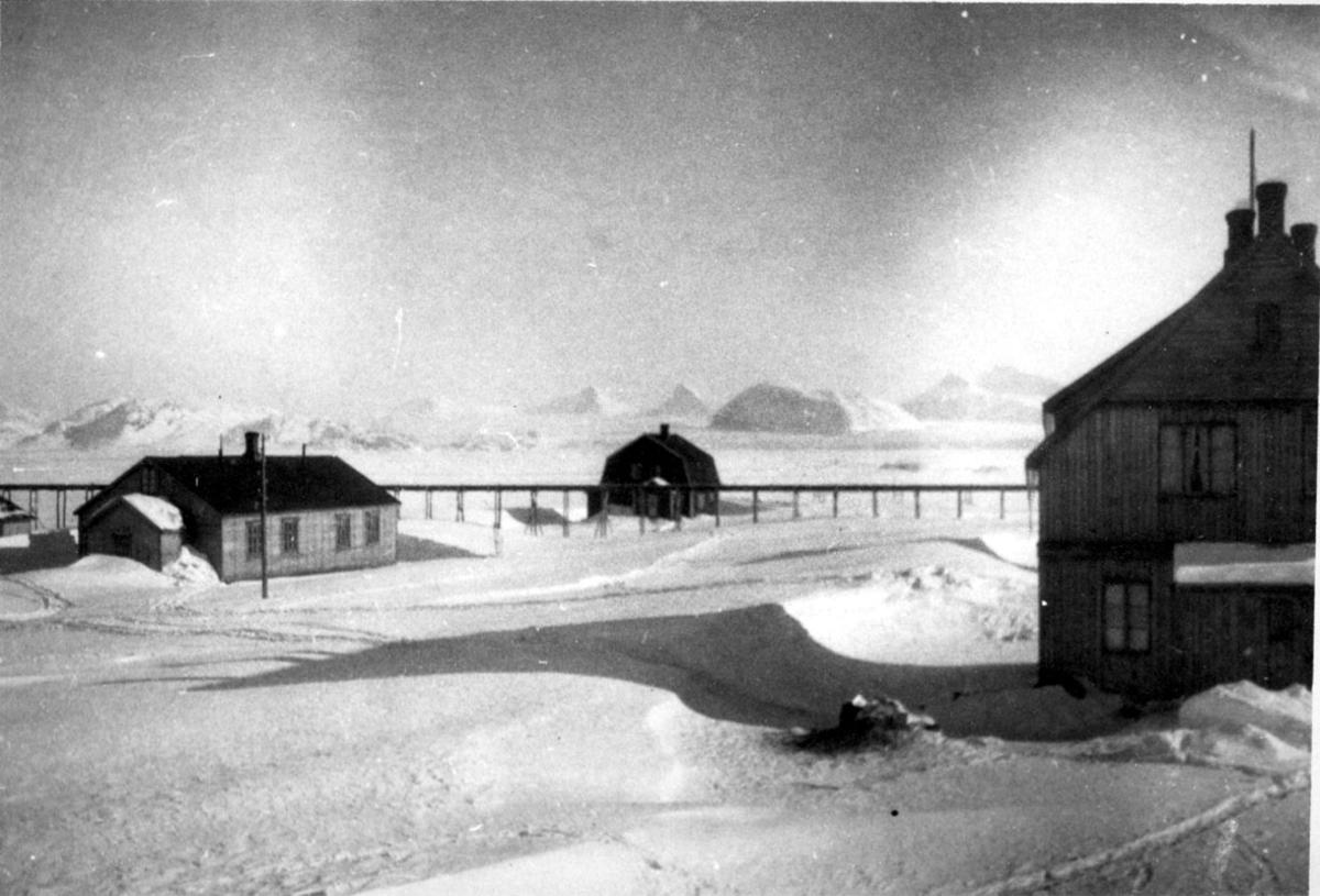 3 bygninger. Jernbanelinje på pæler i bakgrunnen. Snø på bakken