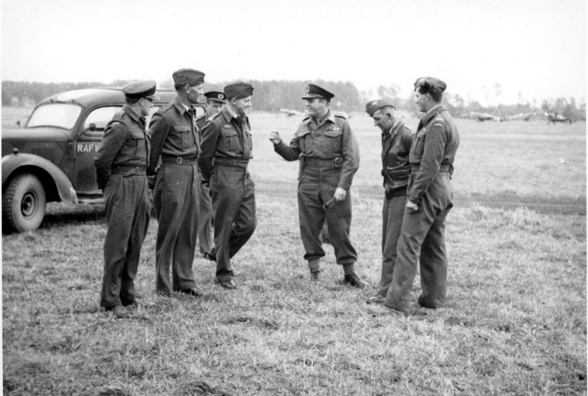 7 personer i militæruniform. Kronprins Olav og 6 andre,  på en åpen plass. Bil bak, med påskrift RAF, på siden. I noen fly i bakgrunnen.