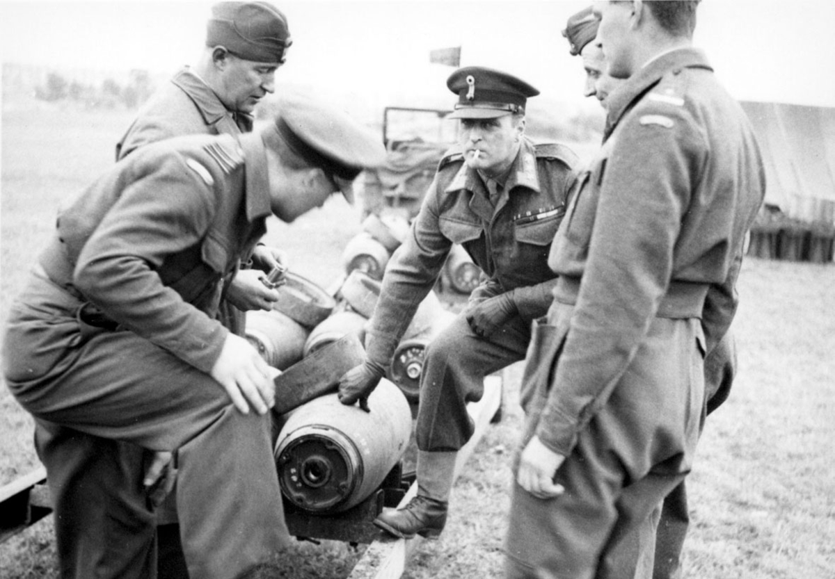 5 personer, i militæruniform, tatt utendørs. Kronprins Olav sammen med 4 andre. Studerer noen flybomber.