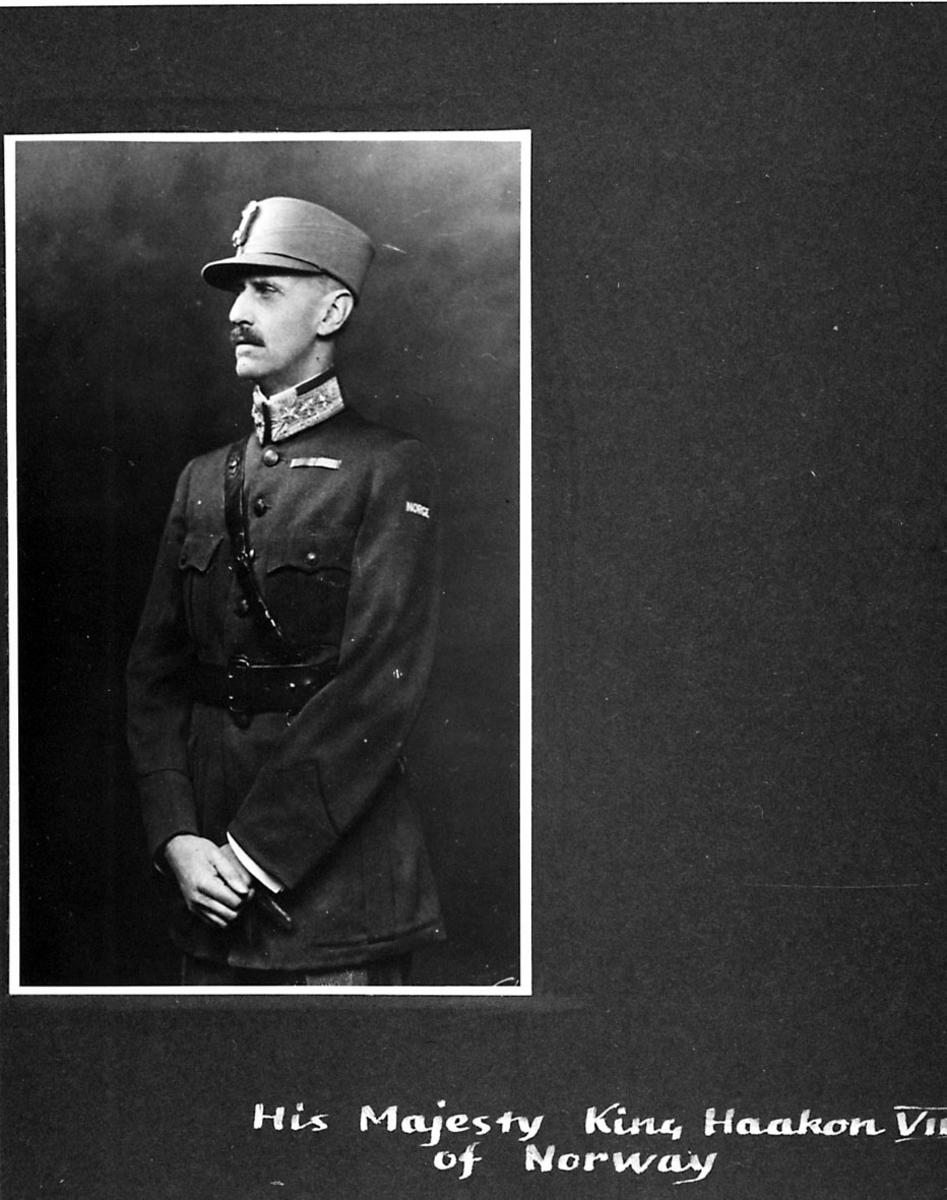 Portrett av Kong Haakon VII, i militæruniform. Håndskrevet tekst under bildet.